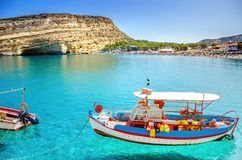 Wooden fishing boats at Matala beach with caves on the rocks, Crete, Greece. Royalty Free Stock Images