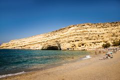 Matala beach with tourists in a sunny summer day. Crete, Greece stock photos