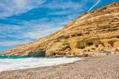 Matala, beautiful beach on Crete island, waves and rocks. Blue sky with clouds. Hippie place, Greece Royalty Free Stock Images