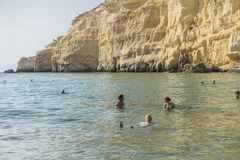 Matala , Red beach. Red Beach, near Matala, Crete, Greece , Europe . Nudist and hippie beach. People swimming in the sea water Stock Image