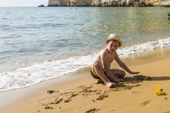 Matala , Red beach. Red Beach,  near Matala, Crete, Greece , Europe . Nudist and hippie beach. The young boy and mum  is playing with sand on the beach Stock Photo