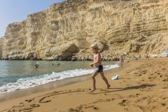 Matala , Red beach. Red Beach,  near Matala, Crete, Greece , Europe . Nudist and hippie beach. The young boy is playing with sand on the beach Stock Photo
