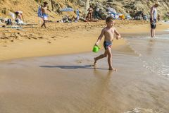 Matala , Red beach. Red Beach,  near Matala, Crete, Greece , Europe . Nudist and hippie beach. The young boy is playing with sand on the beach Royalty Free Stock Photography