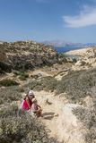 Matala , Red beach. Young child  with mather on the trail of the mountain on a nudist and hippie beach red beach near Matala, Crete, Greece , Europe .Caves Royalty Free Stock Photo