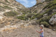Matala , Red beach. Young child on the trail of the mountain on a nudist and hippie beach red beach near Matala, Crete, Greece , Europe .Caves, dwelling hippies Stock Images