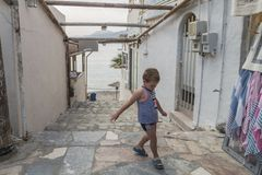 Matala street. Colorful street with  restaurants and taverns in Matala village , Crete , Greece , Europe . View on the sea . And young boy on the street Stock Photography