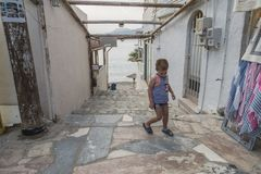 Matala street. Colorful street with  restaurants and taverns in Matala village , Crete , Greece , Europe . View on the sea . And young boy on the street Stock Image