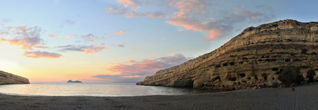 Matala sunsest panorama. Sunset over Matala beach, Crete, with Roman era graves cut into the cliffs on the left. A small community of dropouts and drifters still Royalty Free Stock Photos