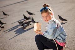 Matande duvor för förtjusande liten flicka utomhus Arkivfoto