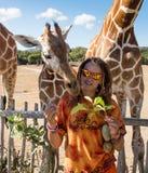 Matande giraff för flicka på zoo Arkivbilder