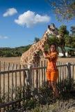 Matande giraff för flicka på zoo Arkivbild