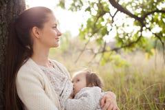 Matande litet barn för moder utomhus Arkivbilder