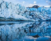 Matanuska Icefall Reflection. The icefall of the Matanuska Glacier is refelcted in a shallow supraglacial lake on top of the ice. The peak of Mt. Wickersham is royalty free stock photo