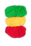 Matasse rosse gialle verdi di lana isolate su un fondo bianco fotografia stock