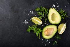 Matbakgrund med avokadot, limefrukt och persilja arkivbild