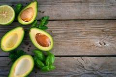 Matbakgrund med avokadot, limefrukt, persilja och basilika på gammalt uppvaktar royaltyfria foton