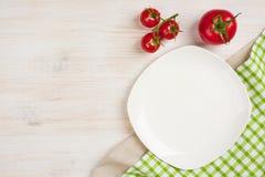 Matbakgrund med den tomma plattan, tomater och kökshandduken Royaltyfria Foton