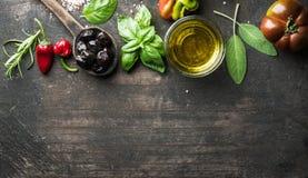Matbakgrund med grönsaker, örter och smaktillsatsen Grekiska svarta oliv, ny basilika, vis man, rosmarin, tomat, pepprar Royaltyfria Foton