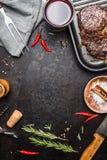 Matbakgrund med grillad biff Ribeye på gallerjärnpannan på lantlig metallbakgrund med rött vin, örter och kryddor Royaltyfri Fotografi