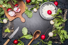 Matbakgrund med nya rädisor, kökhjälpmedel och ny ost Rädisasalladdanande Rädisor och ingredienser för sallad royaltyfri foto