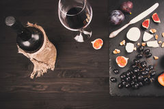 Matbakgrund med rött vin, fikonträd, druvor och ost Royaltyfri Foto