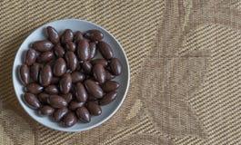 Matbildslutet upp godisen, choklad mjölkar, extra mörka mandelmuttrar Textur på siktsbakgrund på koppplattan royaltyfri bild