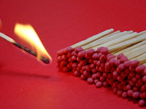 Match 03. Set of matches on a red background with a match on fire Stock Image
