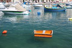 Match box boat. An orange box or a match box boat? A small boat moored in malta's Grand harbour. used as a tender boat to access larger boats moored in the Royalty Free Stock Image