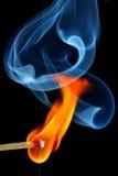 Match bursting to flame. Creating beautiful shapes of smoke stock photography
