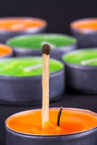 Match. Close up detailed front view of a match, in front of candles, on black background Royalty Free Stock Photos