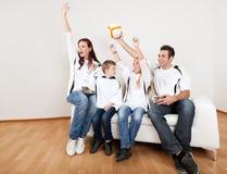 Match de football de observation de jeune famille à la maison Photos libres de droits
