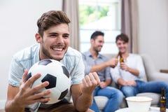 Match de football de observation de jeune homme tandis qu'amis à l'arrière-plan Photo stock