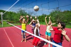 Match de volley parmi les enfants qui jouent activement Photos stock