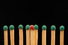 Match en bois rouge se tenant devant huit matchs verts Image libre de droits