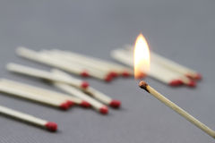 Match. Gray background, a lit match, the release of a faint light stock photography