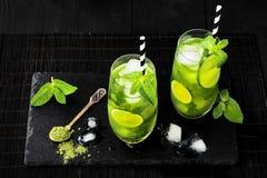 Matcha冰了与石灰和新鲜薄荷的绿茶在黑石板岩背景 超级食物饮料 免版税库存图片
