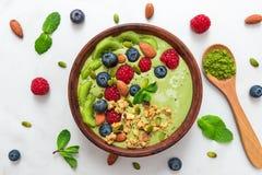 Matcha绿茶圆滑的人碗用新鲜水果、莓果、坚果、种子和格兰诺拉麦片与一把匙子健康早餐 库存照片