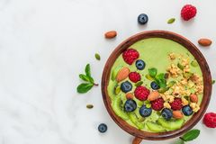 Matcha绿茶圆滑的人碗用新鲜水果、莓果、坚果、种子和燕麦格兰诺拉麦片健康素食主义者早餐 免版税图库摄影