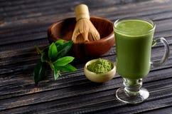 Matcha绿茶在玻璃杯子的拿铁饮料在黑暗的木后面 免版税库存照片