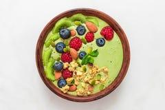 Matcha茶绿色圆滑的人碗用新鲜的莓果、坚果、种子和自创格兰诺拉麦片健康素食主义者饮食早餐 图库摄影