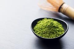 Matcha,在黑碗的绿茶粉末有竹子的在板岩背景扫 复制空间 免版税库存图片