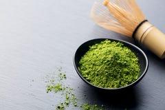 Matcha,在黑碗的绿茶粉末有竹子的在板岩背景扫 复制空间 免版税图库摄影