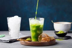 Matcha,绿茶倾吐在木板材的高玻璃的冰茶 灰色蓝色背景 免版税库存图片