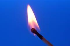 Matcha,被烧的比赛有红色背景点燃了在蓝色背景的火柴 免版税库存照片