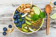 Matcha绿茶早餐superfoods圆滑的人滚保龄球冠上与chia、胡麻和南瓜籽,蜂花粉,格兰诺拉麦片,椰子剥落 库存图片