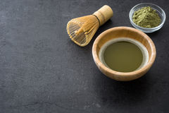 Matcha green tea in a bowl and bamboo whisk on slate Stock Photos