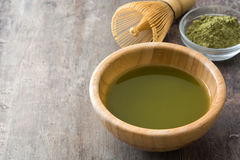 Matcha green tea in a bowl and bamboo whisk, on wood Royalty Free Stock Photography