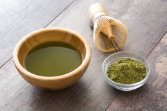 Matcha green tea in a bowl and bamboo whisk, on wood Royalty Free Stock Photos
