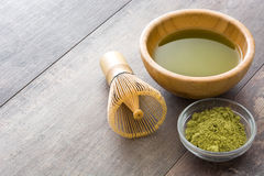 Matcha green tea in a bowl and bamboo whisk, on wood Stock Photos