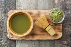 Matcha green tea in a bowl and bamboo whisk, on wood Royalty Free Stock Photo